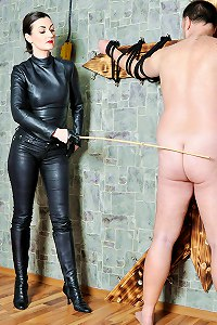 Mistress in leather catsuit employing the cane for an extreme CP test