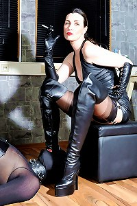 Leather clad mistress smocking while torments her slave